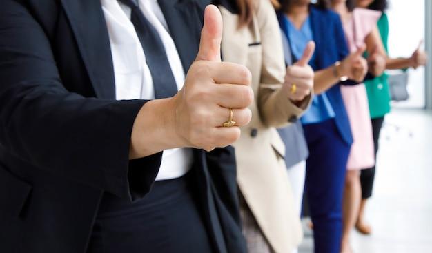 До неузнаваемости неопознанные сотрудники женского пола в деловом костюме показывают большой палец вверх, в то время как другие стоя аплодируют бок о бок, аплодируя руками, показывая теплое приветствие празднования на размытом фоне.