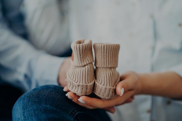 赤ん坊を期待している見分けがつかない女性と男性は、小さなブーツを持っています。家族の母性の父性の概念。未来の両親。誕生