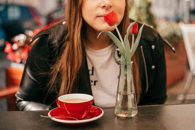 ストリートカフェのテーブルにいる見分けがつかない女性とコーヒーが花の香りを吸い込んでいます。ケータリング施設における顧客志向のアプローチ