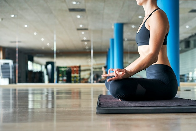 Unrecognizable woman in black sportswear practicing yoga in a gym, doing meditation exercises.
