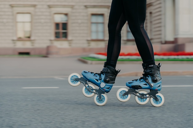 Unrecognizable woman in blue rollerskates moves on road spends free time actively tries new exercise has training poses outdoor near ancient building. rollerblading as hobby. active lifestyle