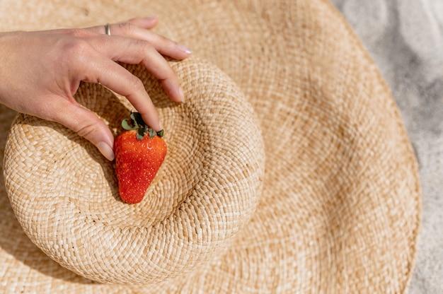 麦わら帽子でイチゴを捕まえている認識できない女性。夏と健康的なライフスタイルのコンセプト