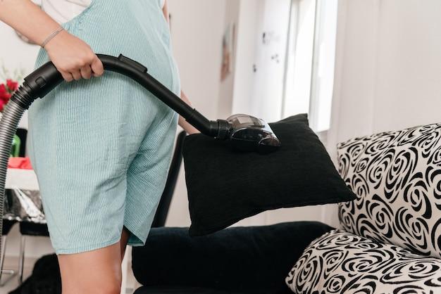 掃除機でソファのクッションを掃除している認識できない女性。