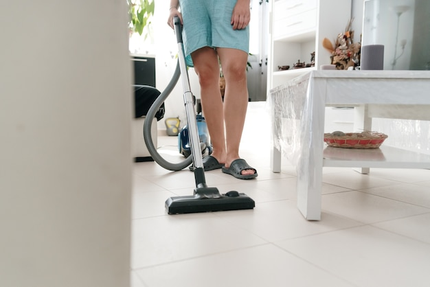 알아볼 수 없는 여자가 진공 청소기로 집을 청소합니다.