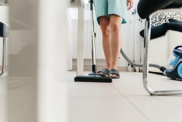 掃除機で家を掃除している認識できない女性。
