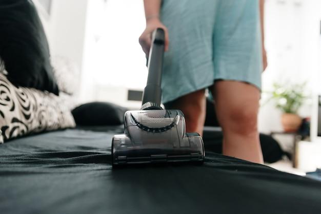 掃除機でソファを掃除している認識できない女性。