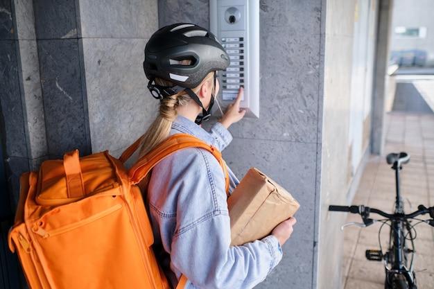 自転車に乗っている認識できない女性の配達人が配達のために家のドアベルを鳴らします