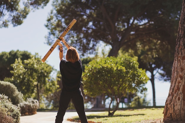 Unrecognizable woman doing exercises with bamboo stick