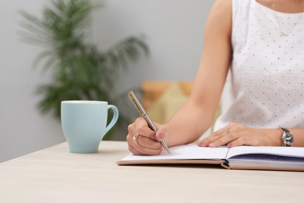 Unrecognizable woman in dress sitting indoors at desk and writing in journal