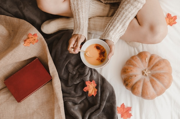 Unrecognizable woman eating near pumpkin and book