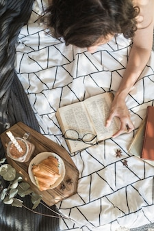 Unrecognizable woman enjoying reading during breakfast in bed