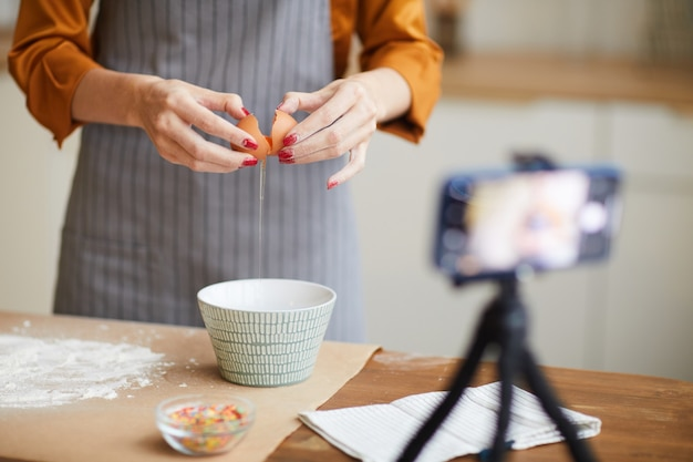 Unrecognizable woman filming baking video