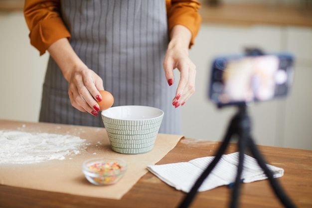 Unrecognizable woman filming cooking video in kitchen