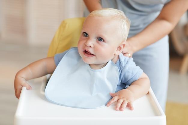 Неузнаваемая женщина сажает своего маленького ребенка в его нагрудник, пока он сидит на высоком стуле