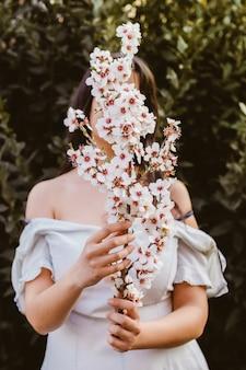 アーモンドの花の枝を持つ認識できない女性の手。素晴らしい春の始まり。セレクティブフォーカス。女性らしさ、フェミニスト、フェミニンなコンセプト。