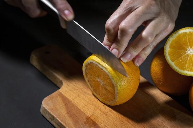 До неузнаваемости женские руки режут свежие здоровые дольки апельсина на деревянной доске