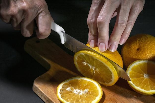 木の板に新鮮な健康的なオレンジスライスを切る認識できない女性の手