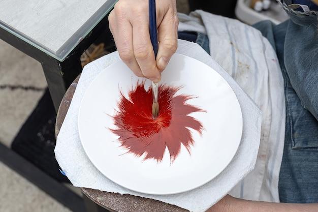 認識できない女性の手がセラミック皿の絵を描いています。職人技のコンセプト
