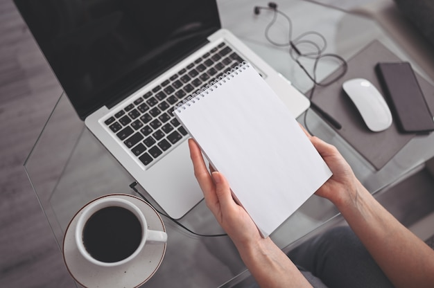 Unrecognizable woman hands writing in empty  notebook and computer. freelancer using smart phone and laptop at home during quarantine. internet marketing, finance, business, remote work concept