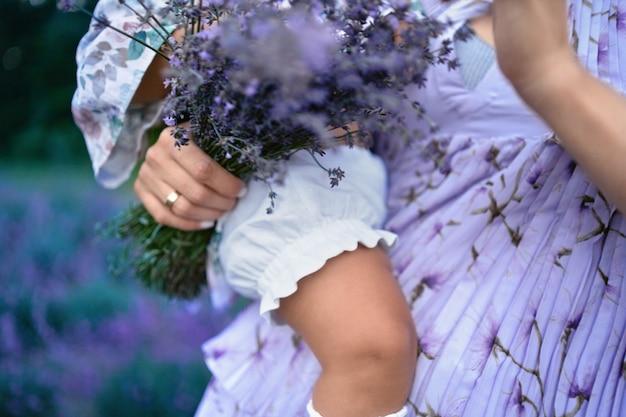 아기와 라벤더 꽃다발을 들고 인식 할 수없는 여자