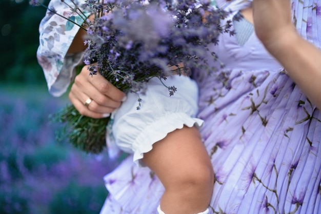 Unrecognizable woman holding baby and lavender bouquet