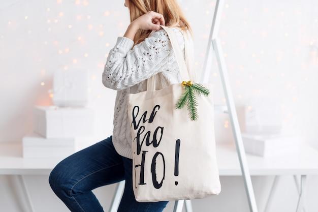 布バッグにクリスマスプレゼントを持って認識できない女性