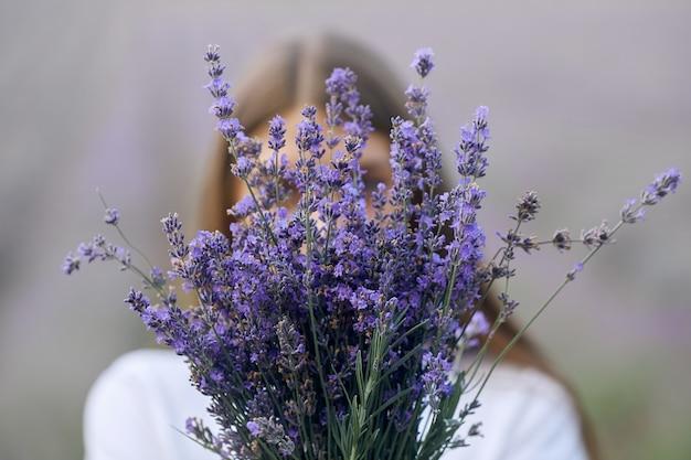 얼굴 근처에 라벤더 꽃다발을 들고 있는 알아볼 수 없는 여자