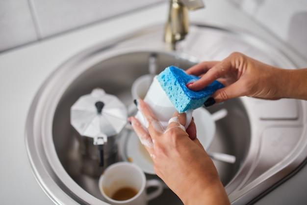До неузнаваемости женщина-домохозяйка моет посуду на кухне дома над раковиной, образом жизни, бытовой техникой.