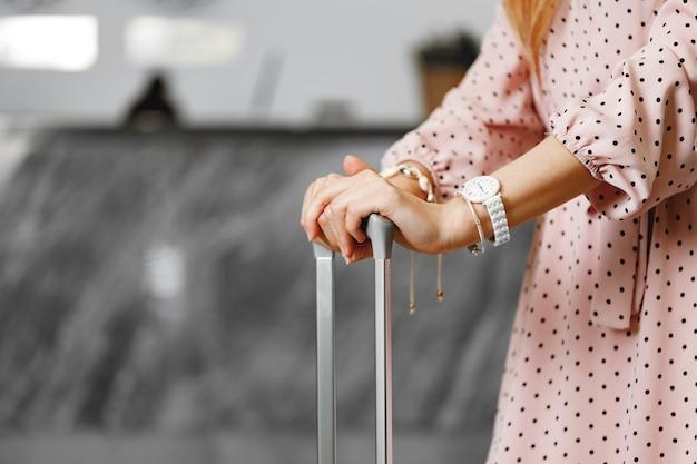 荷物のスーツケースとクローズアップで立っているピンクのドレスの認識できない女性