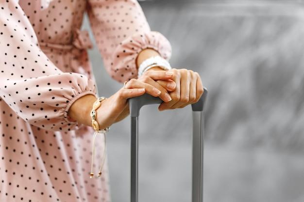 荷物のスーツケースと立っているピンクのドレスの認識できない女性
