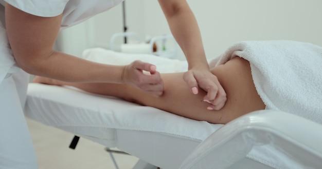 인식할 수 없는 여성이 마사지 테이블에 누워 치료학적 엉덩이 마사지를 즐기고 있습니다. 스파 클리닉에서 안티 셀룰라이트 마사지를 하는 손 안마사 마사지 치료사.
