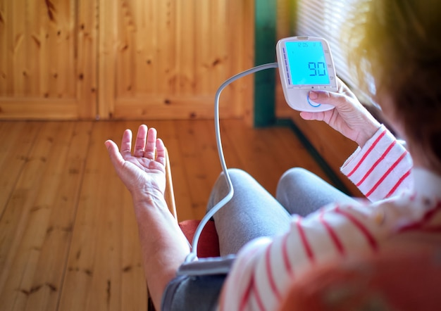 Unrecognizable woman measures blood pressure and pulse rate with digital device while sitting at home