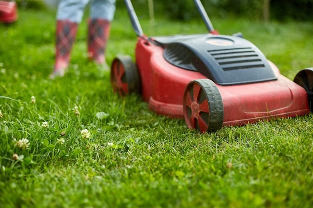 알아볼 수 없는 여성은 가정 정원에서 잔디 깎는 잔디로 잔디를 깎고, 정원사 여성은 일하고, 아름다운 여름 풍경, 햇빛, 모든 목적을 위한 훌륭한 디자인, 원예 개념