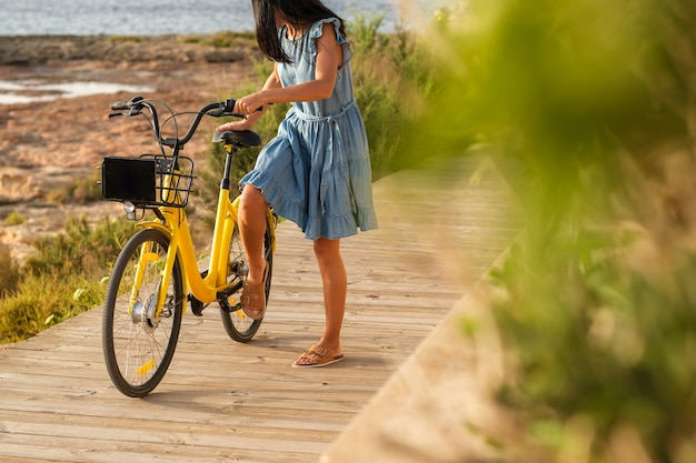 Unrecognizable woman parking yellow bicycle on embankment
