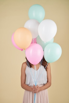Unrecognizable woman posing in studio with her face covered with balloons
