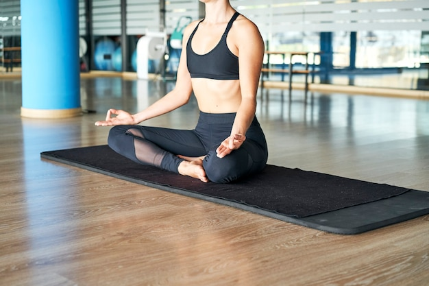 Unrecognizable woman practicing yoga in a gym, doing meditation exercises.