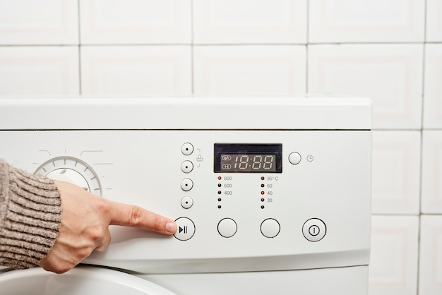 세탁기의 버튼을 누르는 인식할 수 없는 여자