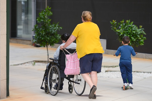 Unrecognizable woman pushing a wheelchair with a disabled person, next to a little boy riding a scooter, rear view on a city street