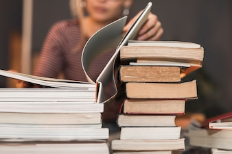 Unrecognizable woman reading book from stack