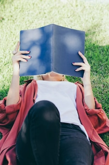 Unrecognizable woman reading on grass