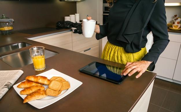 キッチンで速い朝食をとりながら電子タブレットを使用して外出する準備ができている認識できない女性