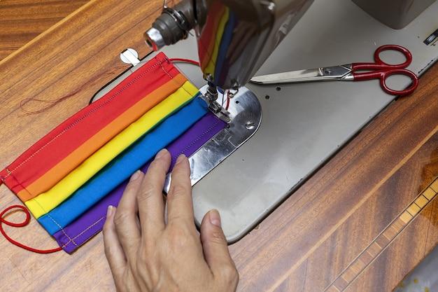 До неузнаваемости женские руки шьют маски для защиты от пандемии covid19. коронавирус самодельный. швейная машина. lgtb; радуга