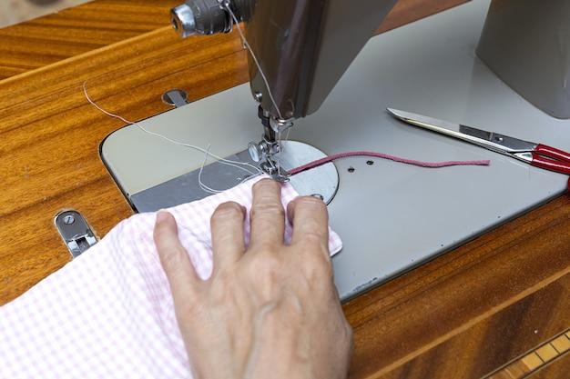 До неузнаваемости женские руки шьют маски для защиты от пандемии covid19. коронавирус самодельный. швейная машина