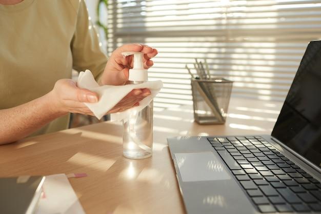 Неузнаваемая женщина дезинфицирует руки, работая за столом в офисе после пандемии, освещенном солнечным светом