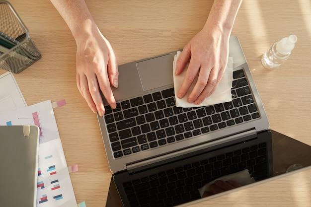 Неузнаваемая женщина дезинфицирует ноутбук, работая за столом в офисе после пандемии, освещенном солнечным светом