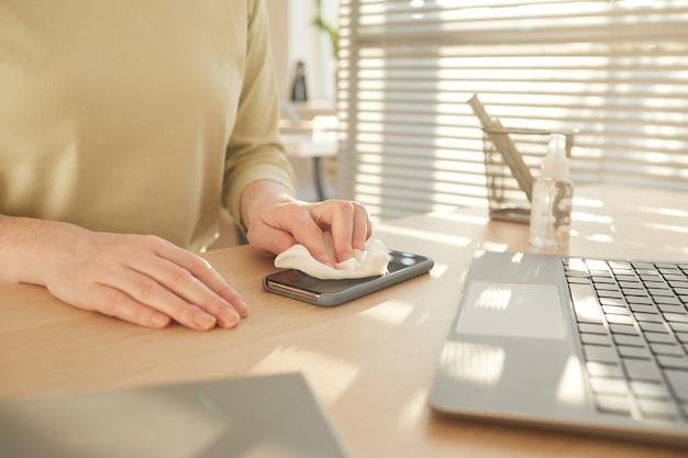 Неузнаваемая женщина дезинфицирует смартфон, работая за столом в офисе после пандемии, освещенном солнечным светом
