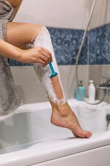 Unrecognizable woman shaving legs in bathroom