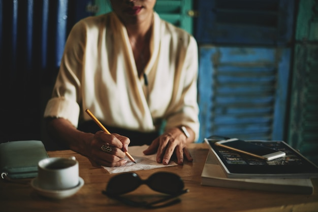 Unrecognizable woman sitting in cafe and drawing on napking