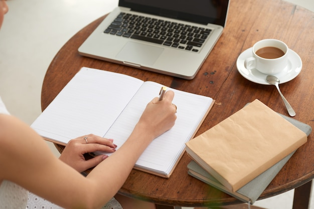 Unrecognizable woman sitting in cafe with laptop and writing in journal