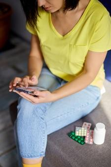 オンライン薬局ストアを使用して錠剤のブリスターパックでソファに座っている認識できない女性